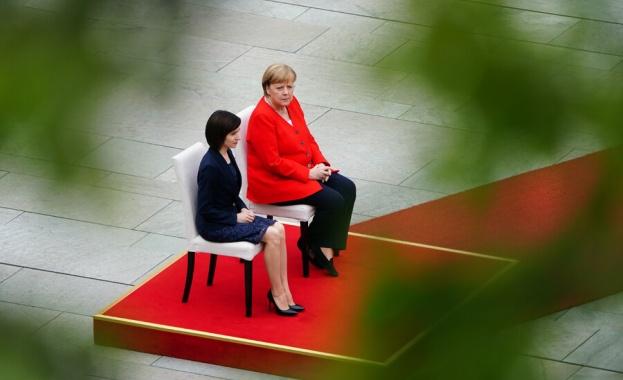 Германският канцлер Ангела Меркел остава седнала при изпълнението на национални
